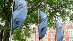 View of the flags with logo of mercedes in the city - breeze blows slowly Stock Footage