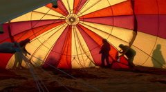 Hot Air Balloon Being Inflated, Interior Backlit By Sun, Silhouettes, Colorful - stock footage