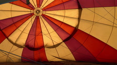 Hot Air Balloon Being Inflated, Interior Backlit By Sun - stock footage