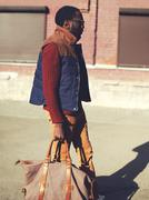 Fashion handsome stylish african man wearing a vest jacket, sweater and bag w - stock photo