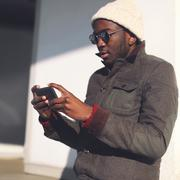 Lifestyle portrait fashion young african man using smartphone in city - stock photo