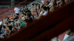 Fans on stadium stands, view through blurred fence, football or soccer match, 4K - stock footage