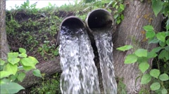 Stock Video Footage of Close up view of Water flows out of the tube one reservoir to another.