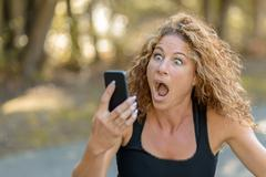 Young woman reacting in horror to a text message Stock Photos