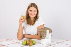 The girl is holding a glass of pear juice - stock photo