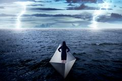Asian business woman standing alone on the paper boat Stock Photos