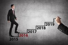 Stock Photo of Business person step into hand drawing stair with 2016 year