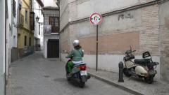 Woman riding motorcycle through narrow cobblestone street in Granada, Spain. Stock Footage