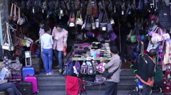 Shoppers in  and out of bag and suitcase shop, in a small commodities market Stock Footage