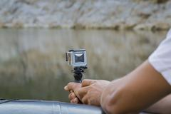 Hand holding small action camera with waterproof case Stock Photos