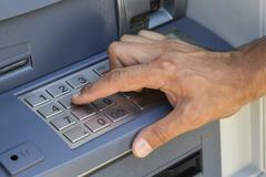 Hand entering pin at ATM machine - stock photo