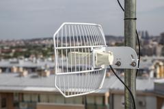 Parabolic grid antenna on apartment building - stock photo