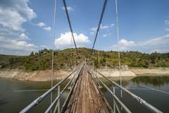 Metal pedestrian suspension bridge Stock Photos