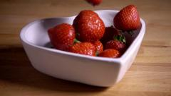 Fresh strawberries dropped into heart shaped bowl, slow motion Stock Footage