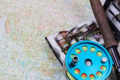 fishing journey with fly-fishing tackles and map - stock photo