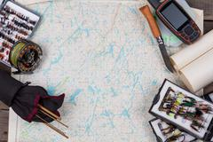 Fly-fishing tackles on paper map background Stock Photos