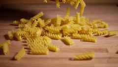 Pasta shapes fall on kitchen table, slow motion Stock Footage