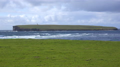 A lighthouse sits on a remote island near the Orkney Islands of Scotland. - stock footage