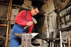 Hands of blacksmith working iron - stock photo