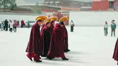 Monks enter Grand Sutra Hall of Labrang Monastery at prayer time - stock footage