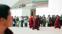Monks enter Grand Sutra Hall of Labrang Monastery at prayer time Stock Footage