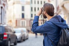 Cheerful bearded man is sightseeing in city - stock photo