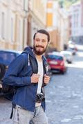 Attractive bearded guy is making journey across town - stock photo