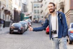 Handsome young male hitchhiker is trying to stop car - stock photo