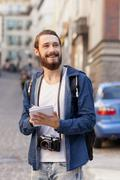 Cheerful bearded man is making his journey in town Stock Photos