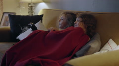 Two sisters sitting on a couch sharing a blanket and watch TV - stock footage
