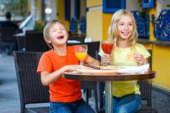 Happy or satisfied boy width girl eating pizza and drinking juice Stock Photos