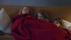 Three sisters sitting on a couch sharing a blanket and watching TV - stock footage