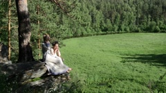 Girls ethnic wear sitting on rocks - stock footage