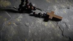 Wooden cross and rosary falling onto stone floor, slow motion Stock Footage