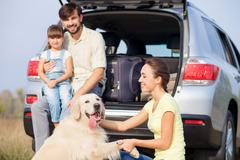 Cute parents are child with pet near transport Stock Photos