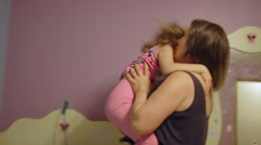 A little girl jumps out of bed in the morning and into her mother's arms Stock Footage