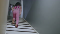 A girl runs up a set of stairs and a dog runs up after her - stock footage