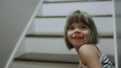 Two girls run up a set of stairs in their house Stock Footage