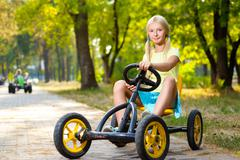 Beautiful smiling little girl riding toy car in summer city park - stock photo