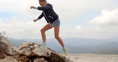 Sporty Woman Standing on Top of Rock Stock Footage