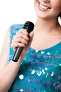 Smiling young woman holding microphone, close up - stock photo