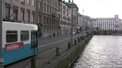 Tram moving alongside canal in Gothenburg Stock Footage