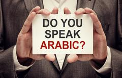 Man wearing suit holding a signboard Do You Speak Arabic - stock photo