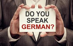 Man wearing suit holding a signboard Do You Speak German Stock Photos