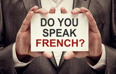 Man wearing suit holding a signboard Do You Speak French - stock photo