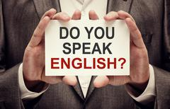 Man wearing suit holding a signboard Do You Speak English Stock Photos