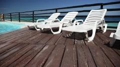 Luxury sunbeds on wooden floor near swimming pool Stock Footage