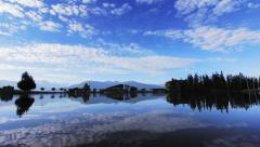 4K timelapse of Clouds over a mountain lake Stock Footage
