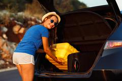 Woman loading luggage into the back of car parked alongside the road - stock photo