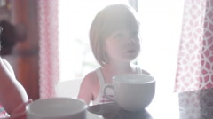 A mother pours scoops of cereal into large mugs for her three daughters - stock footage